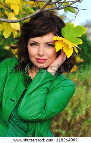Portrait of beautiful young woman in autumn park holding yellow leaf - stock photo