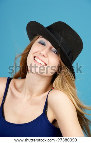 Portrait of beautiful young woman in black hat against blue background - stock photo