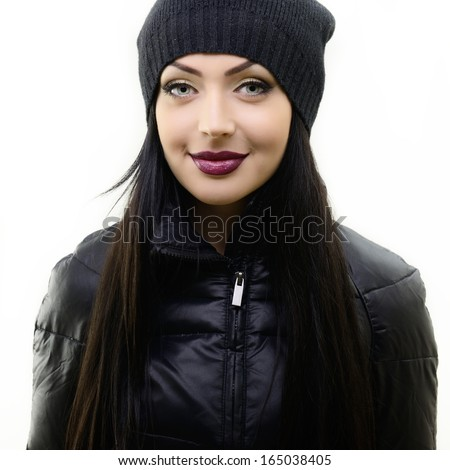 portrait of beautiful young woman in black hat and jacket, studio shot over white - stock photo