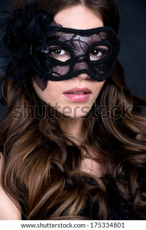 portrait of Beautiful young  woman in black mysterious venetian mask. - stock photo