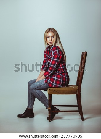 Portrait of beautiful young woman in casual outfit sitting on chair. Caucasian female model looking at camera. - stock photo