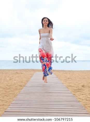 Portrait of beautiful young woman in colorful dress resting at beach in summer - stock photo