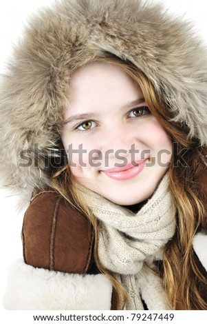 Portrait of beautiful young woman in fur hood of winter coat