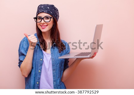 portrait of beautiful young woman in glasses with laptop standing on the pink background - stock photo