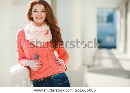 Portrait of beautiful young woman in pink sweater and scarf. Beautiful woman in a sweater in the fall. Portrait of beautiful young woman walking outdoors - stock photo