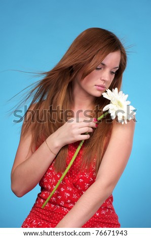 Portrait of beautiful young woman in red sundress over blue background - stock photo