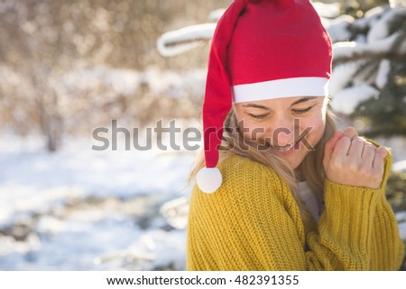 Portrait of beautiful young woman in Santa Claus hat outdoors. Smiling girl walking in a cold winter park and celebrating Christmas.