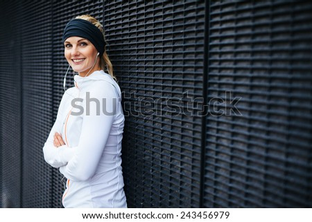 Portrait of beautiful young woman in sports clothing looking at camera smiling. Sporty woman leaning against a wall. - stock photo