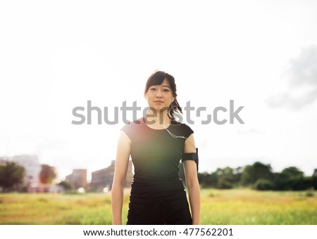 Portrait of beautiful young woman in sportswear standing outdoors in city park on sunny day. Chinese female runner ready for morning workout.