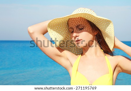 Portrait of beautiful young woman in straw summer hat enjoying sunny day against the sea background, travel concept - stock photo