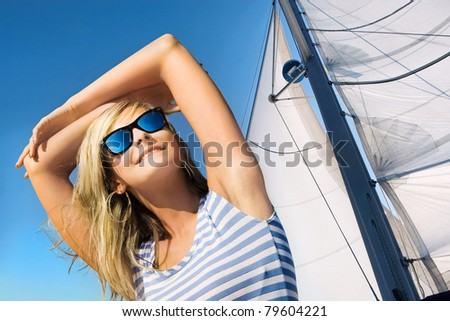 Portrait of beautiful young woman  in sunglasses on sail  background - stock photo