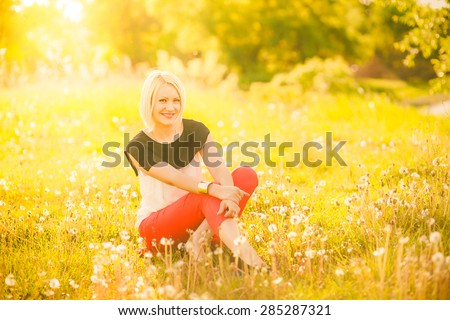 Portrait of beautiful young woman in sunlight outside. Sunset people. Happy girl enjoying nature in summer meadow full of flowers. Charming free blonde sitting in sunny garden. Rest and enjoyment. - stock photo