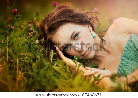 Portrait of beautiful young woman in the sun flare with flowers - stock photo