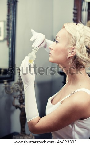Portrait of beautiful young woman in vintage interior smelling a bottle of perfume. Retro style image. - stock photo
