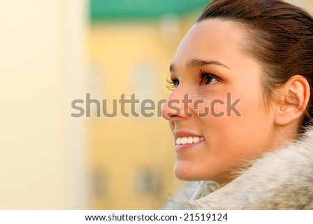 Portrait of beautiful young woman in white fur coat close up.