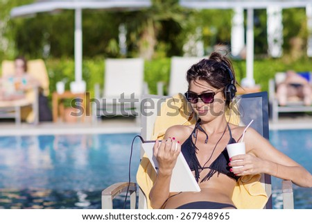 Portrait of beautiful young woman listening music and drinking juice on the pool  - stock photo