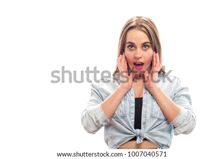 Portrait of beautiful young woman looking surprised at the camera in casual clothes on white background. Copyspace