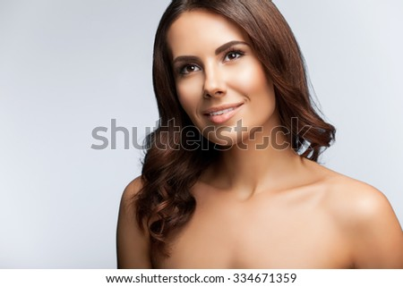 portrait of beautiful young woman, looking up, with naked shoulders, on bright grey background - stock photo