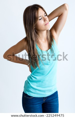 Portrait of beautiful young woman massaging pain back. Isolated on white. - stock photo