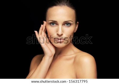Portrait of beautiful young woman model looking at camera. Lovely female with healthy skin isolated on black background. - stock photo