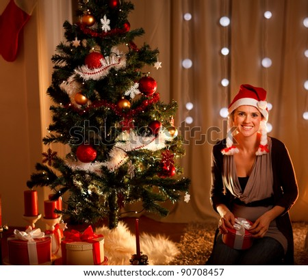Portrait of beautiful young woman near Christmas tree holding gift - stock photo