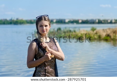 portrait of beautiful young woman near the lake. outdoors - stock photo