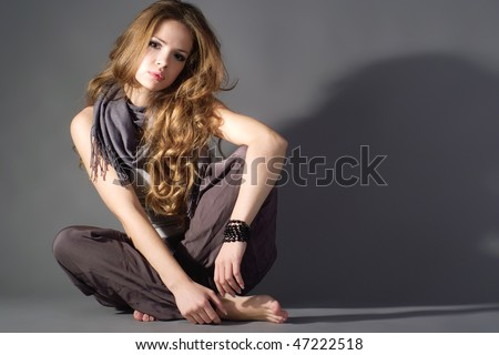 Portrait of beautiful young woman on a grey background - stock photo