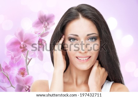 Portrait of beautiful young woman on floral pink background