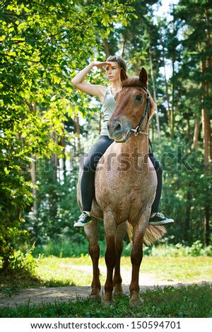 Portrait of beautiful young woman on horseback, against green of summer park. - stock photo