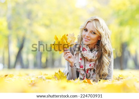 Portrait of beautiful young woman outdoors in autumn park - stock photo