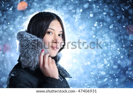 Portrait of beautiful young woman over falling snow background