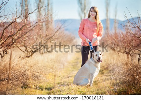 Portrait of beautiful young woman playing with dog at the park - stock photo