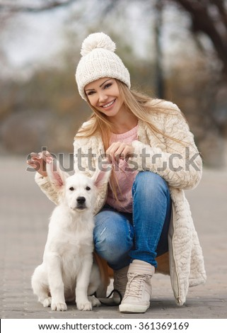 Portrait of beautiful young woman playing with dog in park. portrait of Young girl sitting on the ground with her dog retriever. woman with puppy. Girl with dog. - stock photo