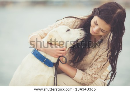 Portrait of beautiful young woman playing with dog on the sea shore - stock photo