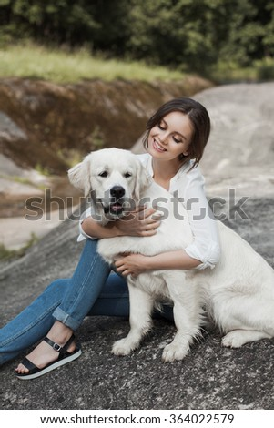 Portrait of beautiful young woman playing with her dog labrador retrievers outdoor in beautiful place