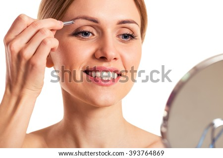 Portrait of beautiful young woman plucking the eyebrows and smiling, isolated on a white background, close-up
