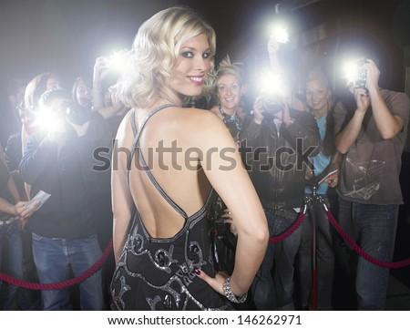Portrait of beautiful young woman posing for paparazzi - stock photo