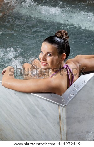 Portrait of beautiful young woman relaxing in a Jacuzzi at spa - stock photo