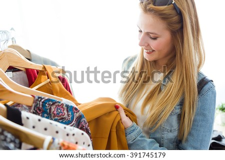 Portrait of beautiful young woman shopping in a clothes shop.