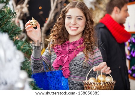 Portrait of beautiful young woman shopping ornaments at Christmas store with man in background - stock photo