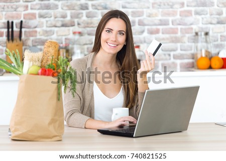 Portrait of beautiful young woman shopping with her card online in the kitchen.