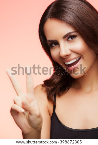 Portrait of beautiful young woman showing two fingers or victory gesture, on light red background - stock photo