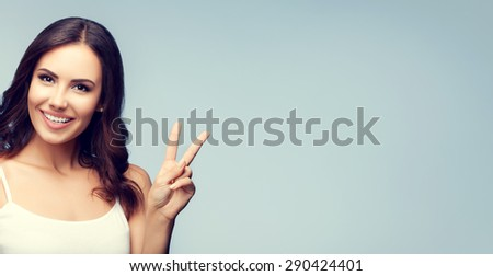Portrait of beautiful young woman showing two fingers or victory gesture, with blank copyspace area for text or slogan - stock photo