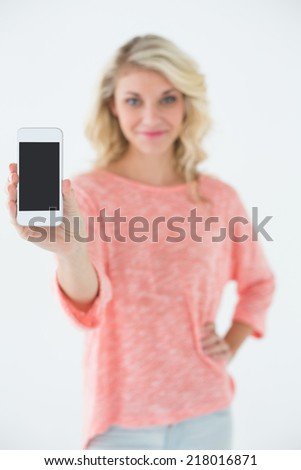 Portrait of beautiful young woman showing you mobile phone over white background - stock photo