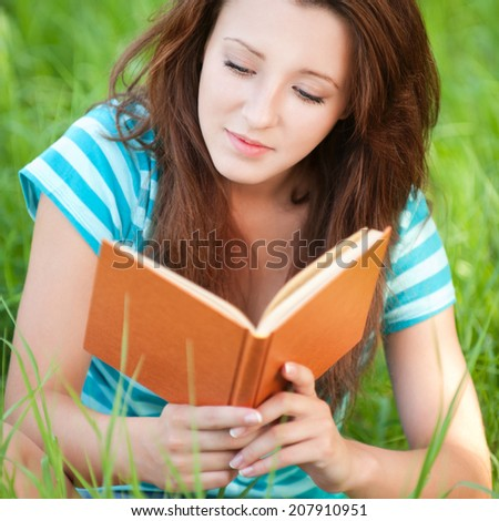 Portrait of beautiful young woman sits on grass and reading book at summer green park - stock photo