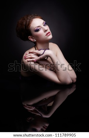 portrait of beautiful young woman sitting at dark mirror table - stock photo