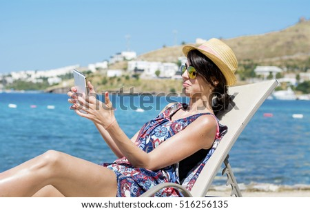 Portrait of beautiful young woman sitting on a sunbed with tablet in the hands on a sea background.Summer holiday