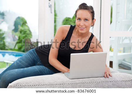 Portrait of beautiful young woman sitting on couch and using laptop - stock photo