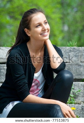 Portrait of beautiful young woman sitting outdoors and smiling