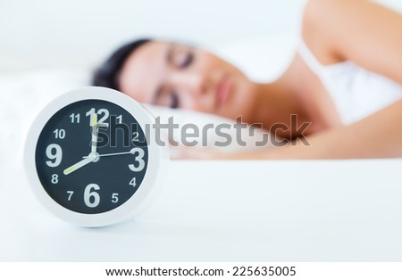Portrait of beautiful young woman sleeping in bed trying to wake up with alarm clock. - stock photo